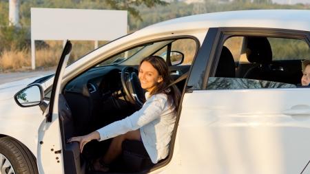 母彼女は後部に乗客として乗って彼女の若い息子を追い払うように車のドアを閉じる