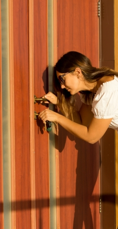 Attractive woman bending down opening a wooden front door with a key in a safety and security concept photo