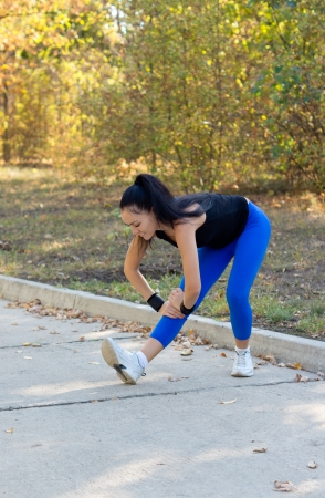 commencing: Fit young woman limbering up stretching her muscles before commencing her workout on a tarred road through a park