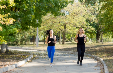 Two athletic attractive women jogging in a park together in a health and fitness concept