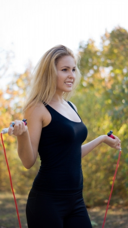 shapely: Shapely blonde woman in sports gear standing with a skipping rope in her hands in a park