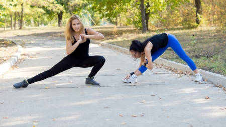 limbering: Two attractive fit young women working out together on a park road doing stretching exercises Stock Photo