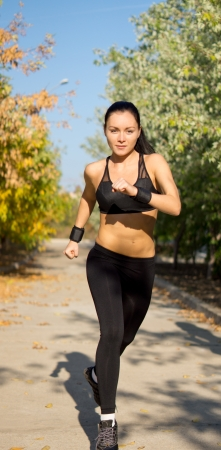 approaching: Female athlete jogging along a rural lane in woodland approaching the camera head on