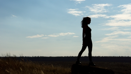 Silhouette of a fit healthy sexy woman standing on the horizon against a late afternoon sky with plenty of copyspace photo