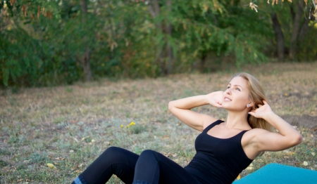 strengthen: Athletic woman doing sit-ups to flex and strengthen her abdominal muscles on a mat in the park with copyspace