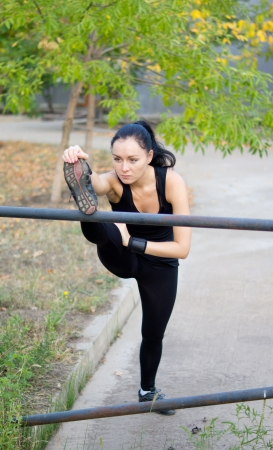 shifted: Dedictaed woman athlete stretching her muscles with her foot raised high on a metal bar and her weight shifted forwards