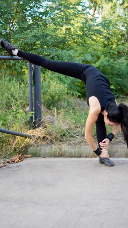 limbering: Supple fit woman working out with her leg raised high in the air behind her as she stretches down to touch her toes on the other foot