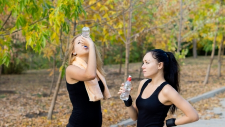 strenuous: Two attractive young women athletes drinking water taking a break from their strenuous workout