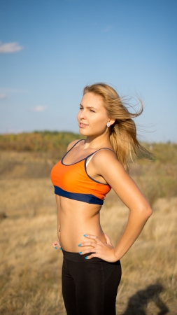 Attractive blonde athletic woman in a sports bra with a bare midriff posing sideways with the wind in her hair in open countryside photo
