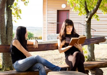 Two young women siting on park bench, reading a book. Stock Photo
