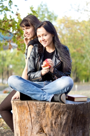 Young woman seated on a sawn off tree trunk outdoors eating an apple while her friend chats on her mobile phone