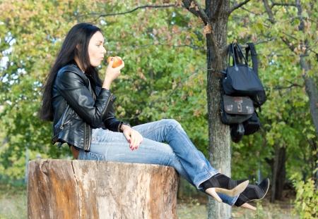 attracive: Stylish modern trendy woman sitting outdoors on a tree stump enjoying an apple