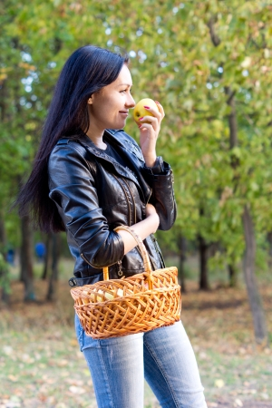 Attractive girl with a basket of freshly picked fruit standing outdoors in the sunshine eating an apple photo