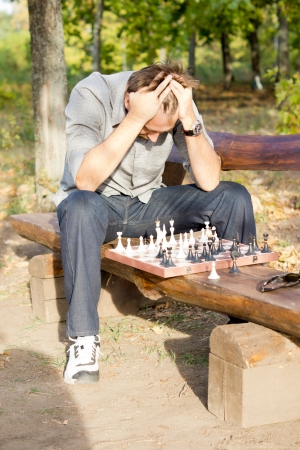 player bench: Chess player in despair sitting straddling a rustic wooden bench with the chess board in front of him and his head in his hands