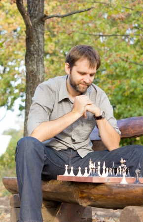 player bench: Low angle view ofa male chess player sitting on a wooden park bench contemplating the chessboard and working out his strategy