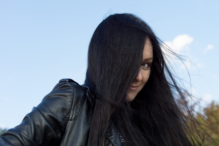 tresses: Woman with long brunette hair blowing in the breeze peering out with one eye from behind her tresses