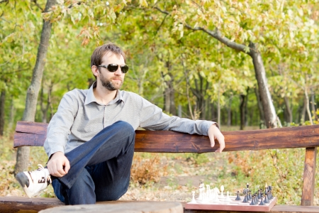 alongside: Pensive young man in sunglasses sitting on a bench in woodland with a chessboard alongside him staring off into the distance deep in thought