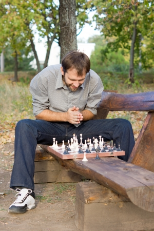 player bench: Young male chess player sitting straddling the seat of a rural wooden bench hunched over the chessboard planning his strategy Stock Photo