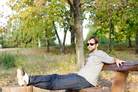 unwinding: Young man relaxing in the sun sitting on a rustic wooden bench with his feet up on a tree stump with copyspace