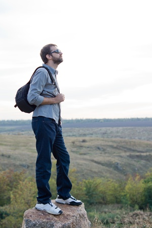 Man exploring with a backpack standing on top of a rock in open countryside with copyspace photo