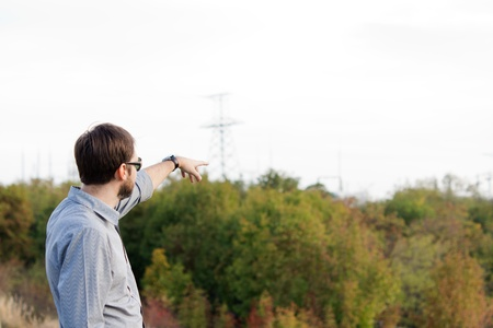 developper: Rear view of a man pointing over open countryside with bush and copy space Stock Photo