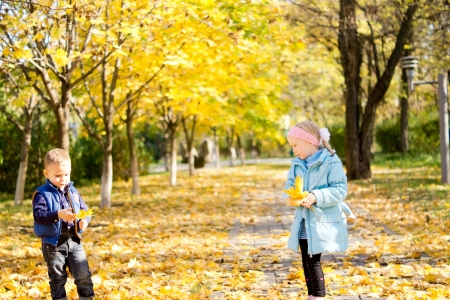 changing seasons: Little girl and boy in an autumn park playing with fallen yellow leaves enjoying the changing seasons with copyspace