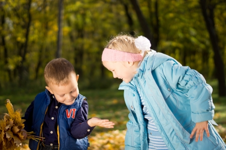 Excited small children watching a bug crawling over the little boy's hand as they gather autumn leaves in woodland Stock Photo - 16009114