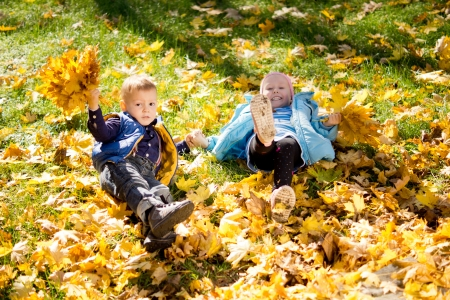 High angle view of two young kids frolicking in yellow autumn leaves that have fallen onto the grass photo