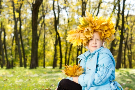 splendour: Proud little girl in autumn splendour sitting with a crown of colourful yellow autumn leaves encircling her head