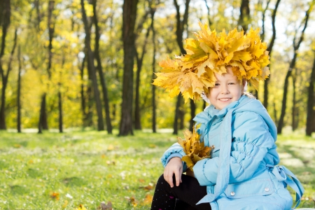 Little girl wearing a crown of colourful yellow autumn leaves on her head as she sits smiling happily in fall woodland photo