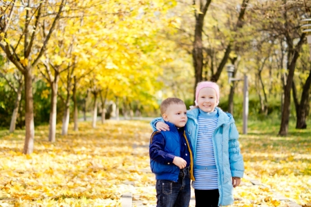 Affectionate young brother and sister standing in a close embrace on a carpet of yellow autumn leaves in a park photo
