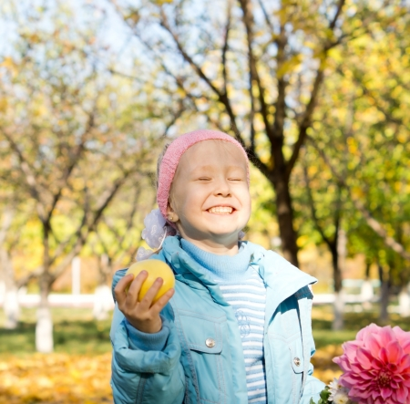 Little girl with a cheesy mischievous grin holding an apple and a fresh pink dahlia standing in colourful autumn countryside photo