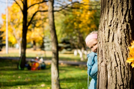peek a boo: Young girl playing peek a boo hiding behimd the trunk of tree in an autumn park and peering out cheekily from the side Stock Photo