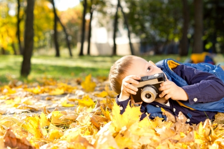 Small boy playing with a vintage slr camera lying down in colourful yellow autumn leaves outdoors in a park photo