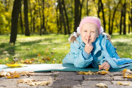 Smiling little girl lying on a mat in the park making shushing gesture raising her finger to her lips as a sign of silence or secrecy Stock Photo