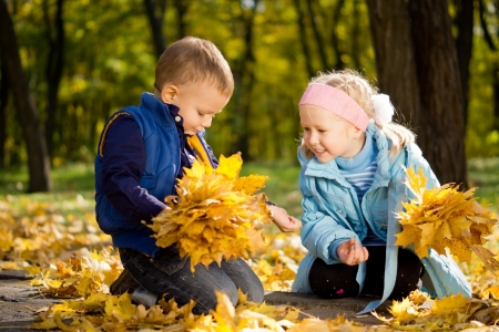 Attractive little brother and sister in autumn woodland photo