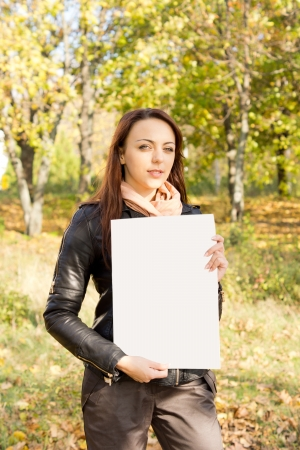 Beautiful trendy young woman holding a blank sign for your text in her hands standing outdoors in woodland Stock Photo - 16055299