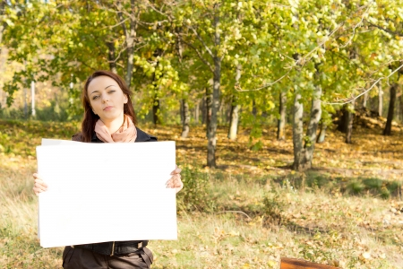 Attractive young woman standing in wooded countryside holding a blank white card for your text or advertisement Stock Photo - 16055304