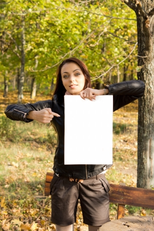 Trendy young woman in shorts holding up a blank sign and pointing to it with her finger while standing alongside a bench in woodland Stock Photo - 16055308