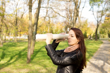 Woman using a rolled newspaper held up to her eye to spy over a distance standing outdoors in a wooded park Stock Photo - 16055277