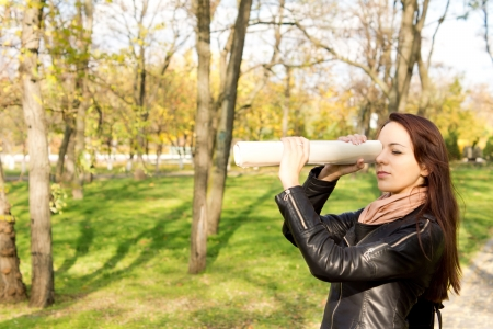 Attractive young brunette woman standing in a park with trees using a rolled newspaper as a spyglass with copyspace photo