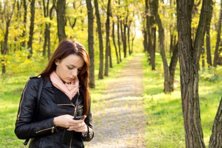 Worried woman standing on a footpath through woodland reading a text message on her mobile phone with copyspace
