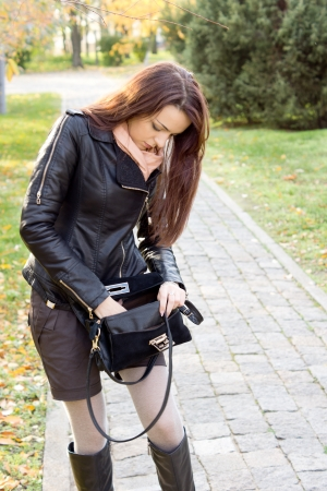 Attractive fashionable woman searching in her handbag for her keys as she stands on the path leading to her home photo