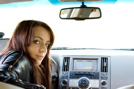 Conductor Atractiva mujer joven mirando hacia atr�s por encima del hombro en el asiento trasero del coche Foto de archivo
