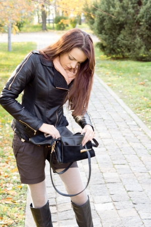 Attractive fashionable woman in shorts and a leather jacket searching in her handbag standing on a paved footpath photo