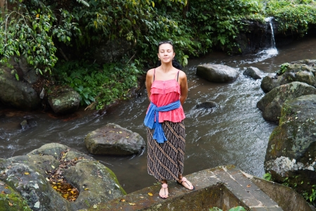 Attractive woman standing above a rocky river with lush vegetation enjoying the peace and tranquillity and the sound of the flowing water Stock Photo - 16524088