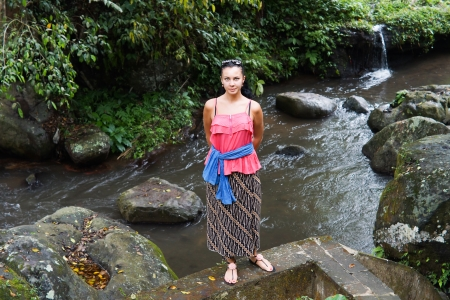 Attractive woman in casual summer clothing standing on a low cement wall above a flowing stream with rocks and lush vegetation Stock Photo - 16524086