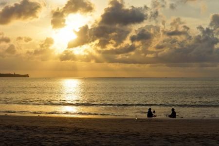 Dos personas siluetas disfrutando de la tranquilidad de un atardecer mar sentado en el borde de las olas cuando el sol se pone en una reflexi�n ornage a trav�s del mar