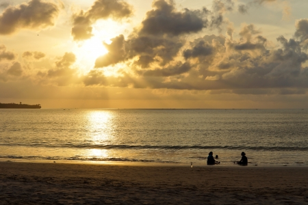 Two silhouetted people enjoying the tranquillity of an ocean sunset sitting at the edge of the surf as the sun casts an ornage reflection across the sea