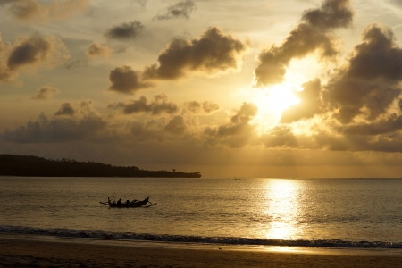 Outrigger canoe paddling just off a sandy beach silhouetted against a golden glow on a sunset ocean as the setting sun breaks through the clouds photo